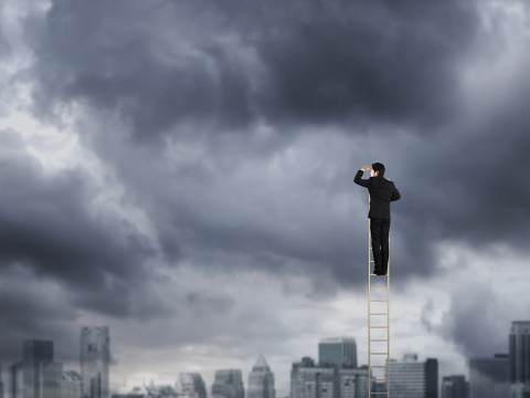 Corporate man climbing a ladder to nowhere