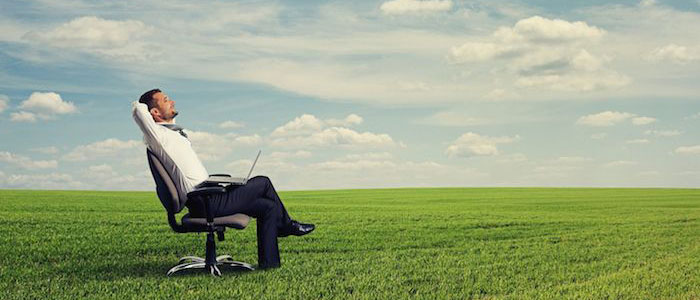 Image of a man sitting on a chair in a field with a laptop on his lap