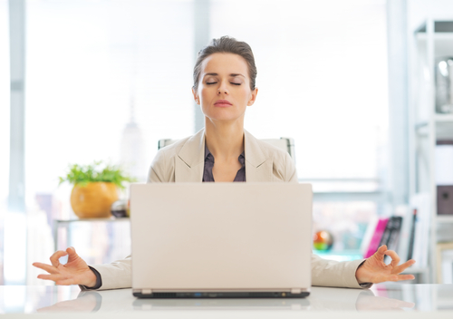 Image of a woman sitting in front of a laptop, her eyes closed and fingertips touching in a meditation pose
