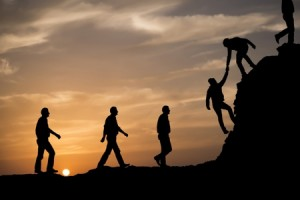 Silhouette of figures walking up a hill, a figure at the top helping the next person up