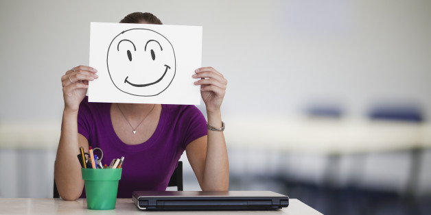 Person sitting at desk holding a piece of paper with a happy face drawn onto it