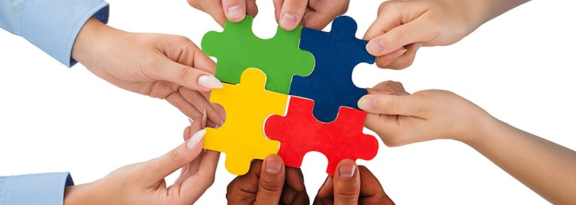 Image of hands holding multi coloured puzzle pieces together