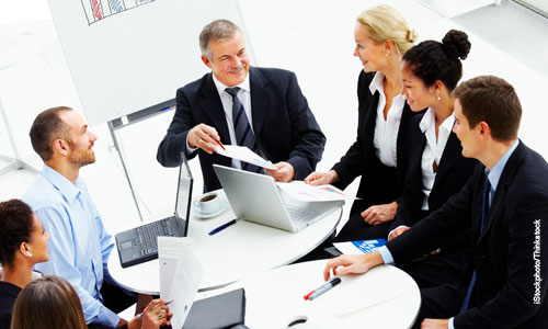 Image of business people sitting around a desk with papers and laptop on the table