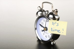 Image of a clock with a post-it note stuck onto it that reads It's Time