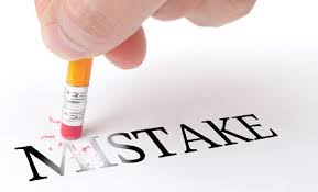The word 'mistake' written on paper with a pencil starting to erase the word
