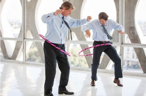 Image of two men in business attire hula-hooping